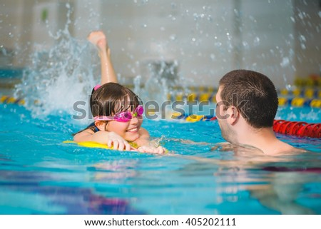 instructor teaches the girl swimming in a pool - stock photo
