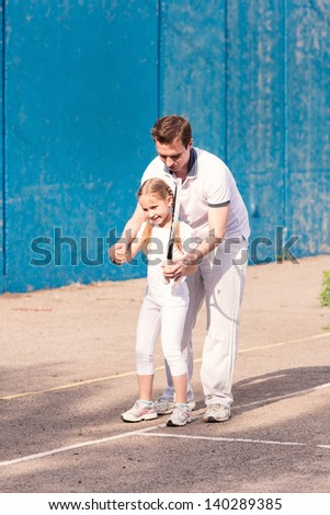 Instructor teaching a child how to play tennis on a court outdoor - stock photo
