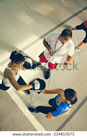 Instructor Teaching Two Young Woman Boxing  - stock photo