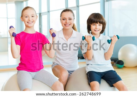 Instructor with kids. Cheerful instructor helping children with exercising in health club  - stock photo