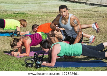 Instructor with tattoo helping bootcamp fitness students - stock photo
