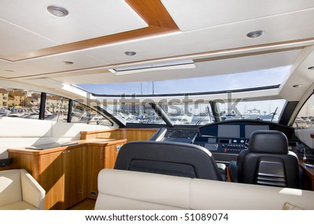 Instrument panel and steering wheel at a motor boat cockpit (yacht control bridge) - stock photo