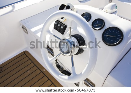 Instrument panel and steering wheel of a motor boat cockpit (yacht control bridge) - stock photo