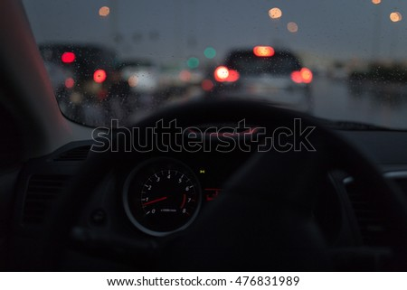 Instrumental cluster of a car in a traffic with rainy & cloudy atmosphere..