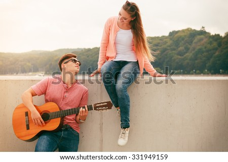 Instruments and musical concept. Young happy couple with instrument man playing classic guitar dating outdoor at sea. - stock photo