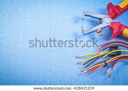 Insulated wire strippers electrical cables on blue background copy space electricity concept. - stock photo