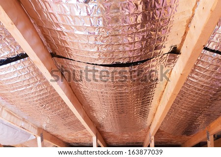 Insulating of attic with fiberglass cold barrier and reflective heat barrier used as baffle between the attic joists to increase the ventilation to reduce humidification - stock photo