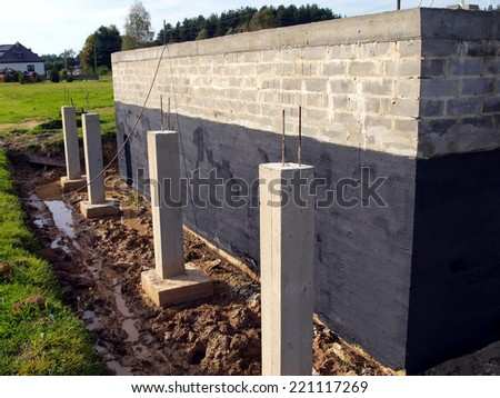 insulation against moisture foundation wall of the building made ??of concrete blocks for the clay soil - stock photo