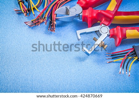 Insulation strippers set of electric wires cutting pliers on blue background electricity concept. - stock photo
