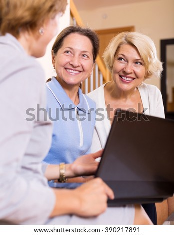 Insurance agent consulting female pensioners at home - stock photo