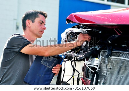 Insurance agent inspecting car damage. - stock photo
