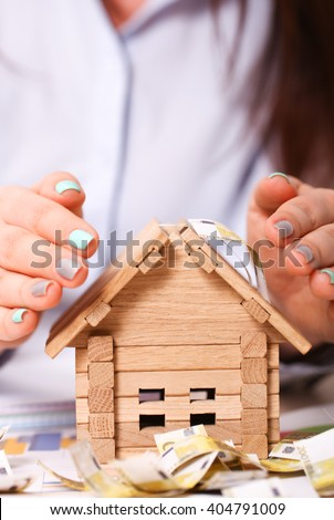 Insurance agent protecting house with her hands