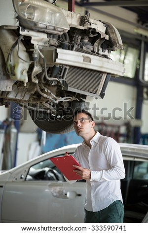 insurance agent writing on clipboard assessment on car damage - stock photo