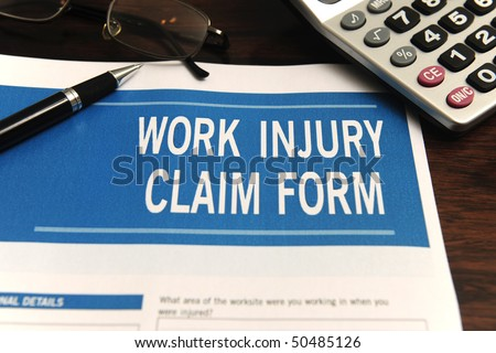 insurance: blank work injury claim form on desk (Form was created for this shooting - no property release necessary) - stock photo