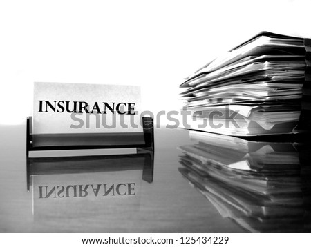 Insurance card on desk with files - stock photo