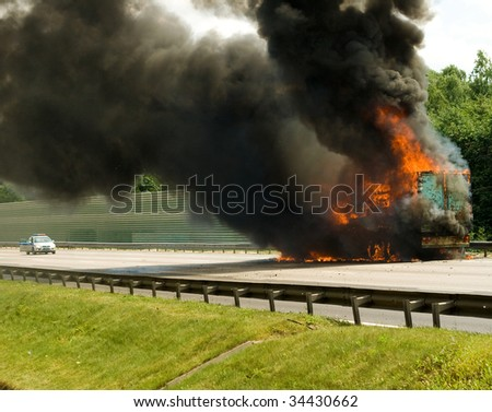 insurance case with truck in fire ith black smoke - stock photo