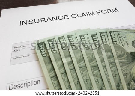 Insurance claim form and assorted money                                - stock photo