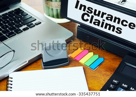 Insurance Claims- Ring Binder on Office Desktop with Office Supplies. Business Concept on Toned and Blurred Background - stock photo