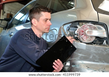 Insurance  employee working with a car. - stock photo