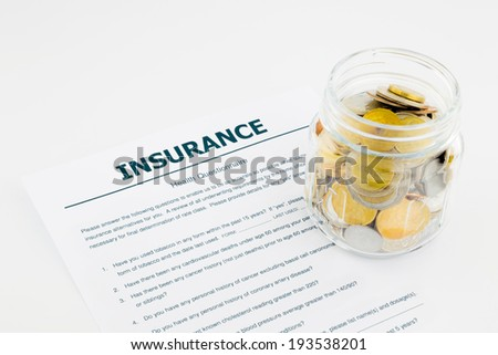 insurance health questionnaire and coins on white background - stock photo
