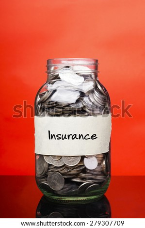 Insurance label on glass jar with coins - stock photo