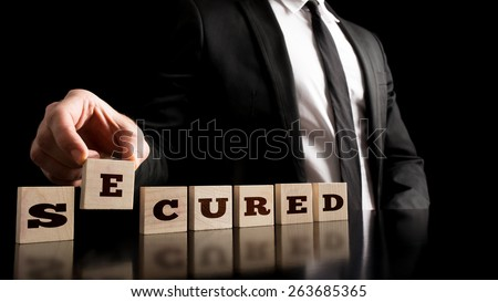 Insurance market concept - Businessman Arranging Small Wooden Blocks with word Secured on a Pure Black Background. - stock photo