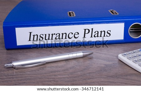 Insurance Plans - blue binder with calculator and pen on desk in the office - stock photo