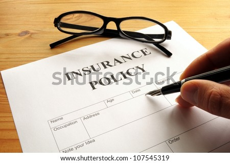 insurance policy form on desk in office showing risk concept - stock photo