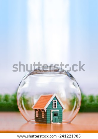 Insured house concept. Toy house protected in glass sphere with copy space above - stock photo