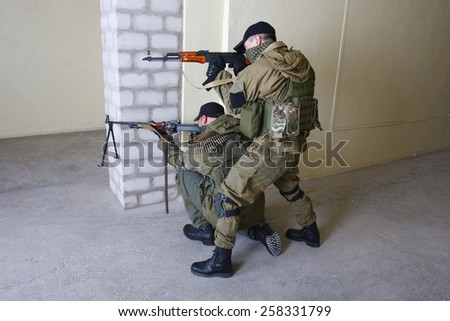 insurgents with AK 47 ang RPD gun inside the building - stock photo