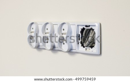 Integrated electrical outlet in the room on the background of the white wall