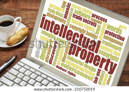 intellectual property word cloud on digital tablet with a cup of coffee - stock photo