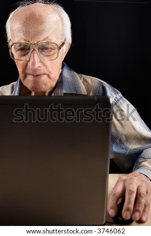 Intellectual senior man works on the laptop late at night - stock photo