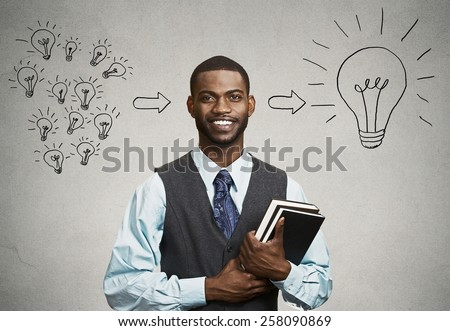 Intelligence knowledge. Closeup smart happy handsome man confident student holding books has big ideas isolated on gray wall background. Positive face expression emotion attitude life perception  - stock photo