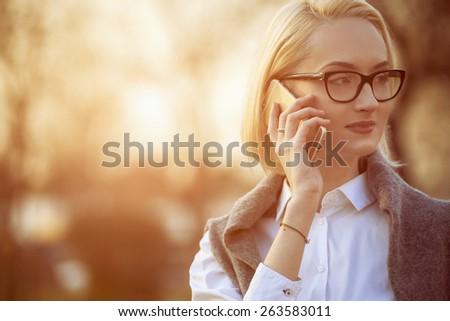 intelligent beautiful woman is using her smart phone, sunset background - stock photo