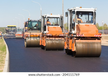 Intelligent Compaction for Asphalt Concrete Surface with Road Crews Rollers during Road Construction Works - stock photo