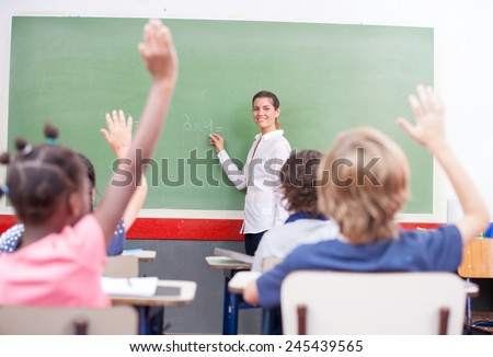 Intelligent group of young school children raising their hands in the air to answer a question posed by the female teacher, view from behind. - stock photo