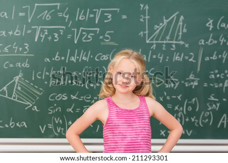 Intelligent little girl child prodigy in class standing confidently in front of a blackboard covered in mathematical equations with her hands on her hips smiling at the camera - stock photo