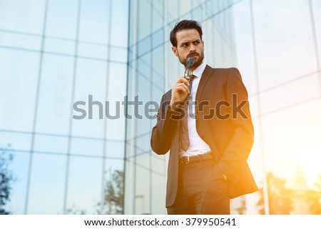 Intelligent man holding glasses near mouth and looking on something with angry face during work break outside, young male lawyer resting after losing court case while standing outdoors near skyscraper - stock photo