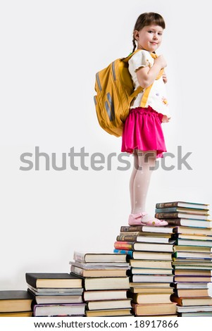 Intelligent schoolgirl standing on top of book pile and looking at camera - stock photo