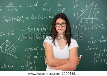 Intelligent young female maths student or teacher wearing glasses standing in front of a chalkboard with mathematical equations with folded arms and a piece of chalk in her hand - stock photo