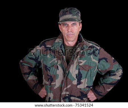 Intense army veteran staring at the viewer with arms akimbo.