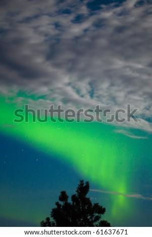 Intense Aurora borealis showing between clouds during moon lit night. - stock photo