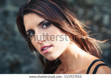 Intense beautiful girl portrait. Stone wall background.