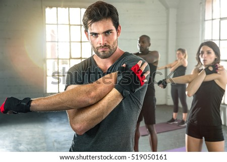 Intense Focused Man Serious Expression Stretch Before Workout In Group Exercise Gym