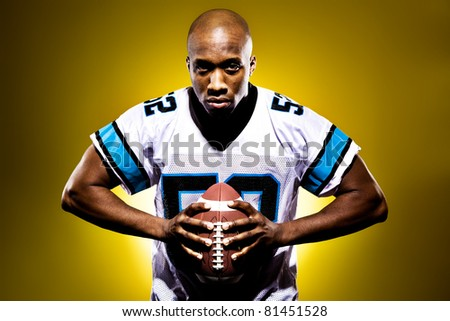Intense football player holding a ball against a golden background - stock photo