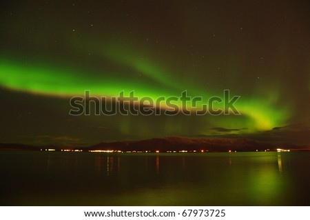 Intense northern lights (Aurora borealis) on the Reykjavik coast, Iceland - stock photo
