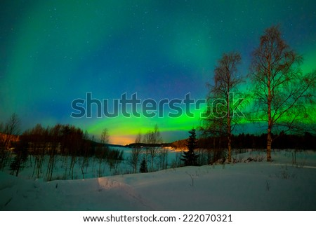 Intense northern lights - Aurora borealis over Lake in Finland - stock photo