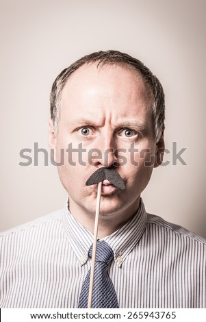 Intense portrait of a man wearing a shirt and tie with bug eyes and a fake mustache. - stock photo