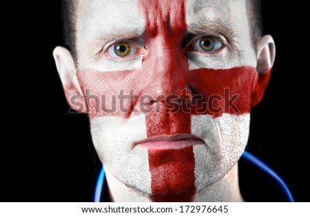 Intense stare from a football fan with their face painted with the English flag. - stock photo
